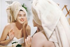 Skin Care concept. Young happy woman in towel making facial massage with organic face scrub and looking at mirror in stylish stock photo