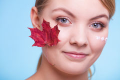 Skin care. Face of young woman girl with red maple leaf. Stock Image