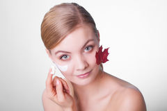 Skin care. Face of young woman girl with red maple leaf. Stock Images