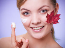 Skin care. Face of young woman girl with red maple leaf. Skincare habits. Face of young woman with leaf as symbol of red capillary skin on gray. Girl taking Royalty Free Stock Photography