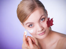 Skin care. Face of young woman girl with red maple leaf. Stock Photos