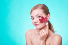 Skin care. Face of young woman girl with red maple leaf. Stock Photography