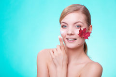 Skin care. Face of young woman girl with red maple leaf. Stock Photo