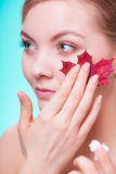 Skin care. Face of young woman girl with red maple Stock Photo