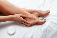 Skin care for feet. Woman caring about her feet and putting hydrating cream on it Stock Images