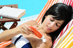 Skin Care in Pool. Woman blocking sun applying protection on her skin at poolside in summer Stock Images