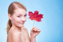 Skin care. Portrait of young woman girl with red maple leaf. Stock Photography