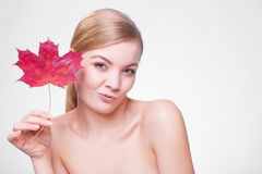 Skin care. Portrait of young woman girl with red maple leaf. Skincare habits. Portrait of young woman with leaf as symbol of red capillary skin on gray. Face of Stock Images