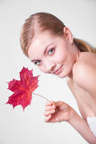 Skin care. Portrait of young woman girl with red maple leaf. Royalty Free Stock Image