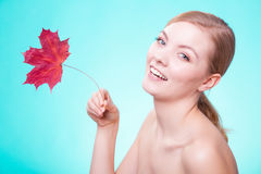 Skin care. Portrait of young woman girl with red maple leaf. Royalty Free Stock Photography