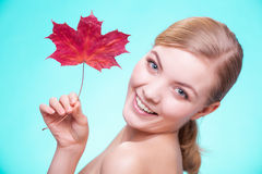 Skin care. Portrait of young woman girl with red maple leaf. Royalty Free Stock Photo