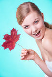 Skin care. Portrait of young woman girl with red maple leaf. Stock Photo