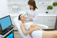 Skin Care. Pregnant Woman On Face Cleansing At Beauty Clinic stock photography