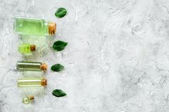 Skin care products with tea tree oil in bottles on grey stone background top view copyspace. Skin care products with tea tree oil in bottles on grey stone Stock Images