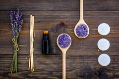 Skin care and relax. Cosmetics and aromatherapy concept. Lavender spa salt and oil on dark wooden background top view.  stock photos