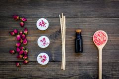 Skin care and relax. Cosmetics and aromatherapy concept. Rose spa salt and oil on dark wooden background top view Stock Images