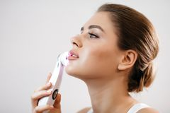 Skin Care. Side portrait of the charming healthy fresh woman with natural make-up using the electric facial massager at. White background Stock Photos
