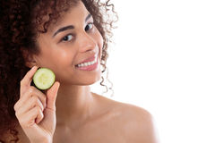 Skin care with some help from nature. Shot of a young woman holding a slice of cucumber royalty free stock images