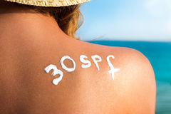 Skin care and sun protection. Woman with sunscreen lotion on back at the sea shore Stock Photography
