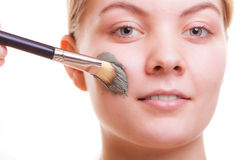 Skin care. Woman applying clay mask on face. Spa. Royalty Free Stock Image