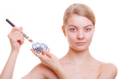 Skin care. Woman applying clay mask on face. Spa. Stock Photo