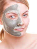 Skin care. Woman applying clay mask on face. Spa. Stock Photos