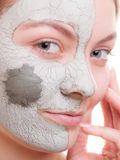 Skin care. Woman applying clay mask on face. Spa. Stock Image