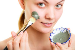 Skin care. Woman applying clay mud mask on face. Skin care. Woman applying with brush clay mud mask on face isolated. Girl taking care of dry complexion. Beauty Royalty Free Stock Images