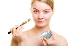 Skin care. Woman applying clay mud mask on face. Royalty Free Stock Photo