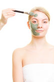 Skin care. Woman applying clay mud mask on face. Royalty Free Stock Photography