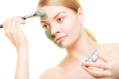 Skin care. Woman applying clay mud mask on face. Royalty Free Stock Image