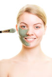 Skin care. Woman applying clay mud mask on face. Stock Photography