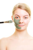 Skin care. Woman applying clay mud mask on face. Royalty Free Stock Photos