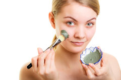 Skin care. Woman applying clay mud mask on face. Stock Photos