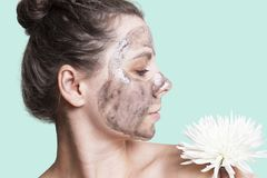 Skin care. Woman with black facial mask and white flower Stock Photos