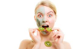 Skin care. Woman in clay mask on face and kiwi Royalty Free Stock Photography