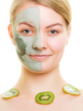Skin care. Woman in clay mask on face and kiwi Royalty Free Stock Images