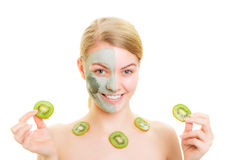 Skin care. Woman in clay mask on face and kiwi Stock Image