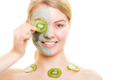 Skin care. Woman in clay mask on face and kiwi Royalty Free Stock Photo