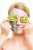 Skin care. Woman in clay mask with kiwi on face Royalty Free Stock Photo
