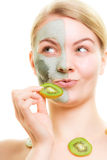 Skin care. Woman in clay mask with kiwi on face Royalty Free Stock Images