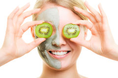 Skin care. Woman in clay mask with kiwi on face Stock Images