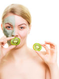 Skin care. Woman in clay mask with kiwi on face Royalty Free Stock Photos