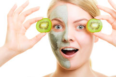 Skin care. Woman in clay mask with kiwi on face Stock Photo