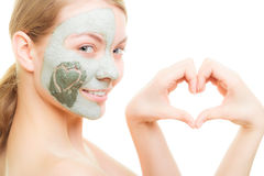 Skin care. Woman in clay mud mask on face. Beauty. Skin care. Woman in clay mud mask on face with heart on cheek isolated on white. Girl showing symbol of love Stock Photography