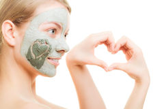 Skin care. Woman in clay mud mask on face. Beauty. Skin care. Woman in clay mud mask on face with heart on cheek isolated on white. Girl showing symbol of love Royalty Free Stock Image