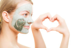 Skin care. Woman in clay mud mask on face. Beauty. Skin care. Woman in clay mud mask on face with heart on cheek isolated on white. Girl showing symbol of love Stock Images