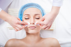 Skin care - woman cleaning face by beautician Stock Images