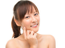 Skin care woman putting face cream. Touching her cheek. Facial beauty closeup of beautiful mixed race Asian female model isolated on white background Royalty Free Stock Photos