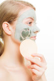 Skin care. Woman removing clay mud facial mask. Skin care. Woman removing green clay mud facial mask with sponge isolated on white. Girl taking care of dry Royalty Free Stock Images